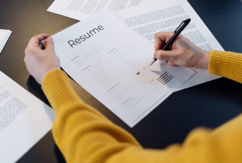 Personne en train de rédiger son CV et sa lettre de motivation pour une candidature
