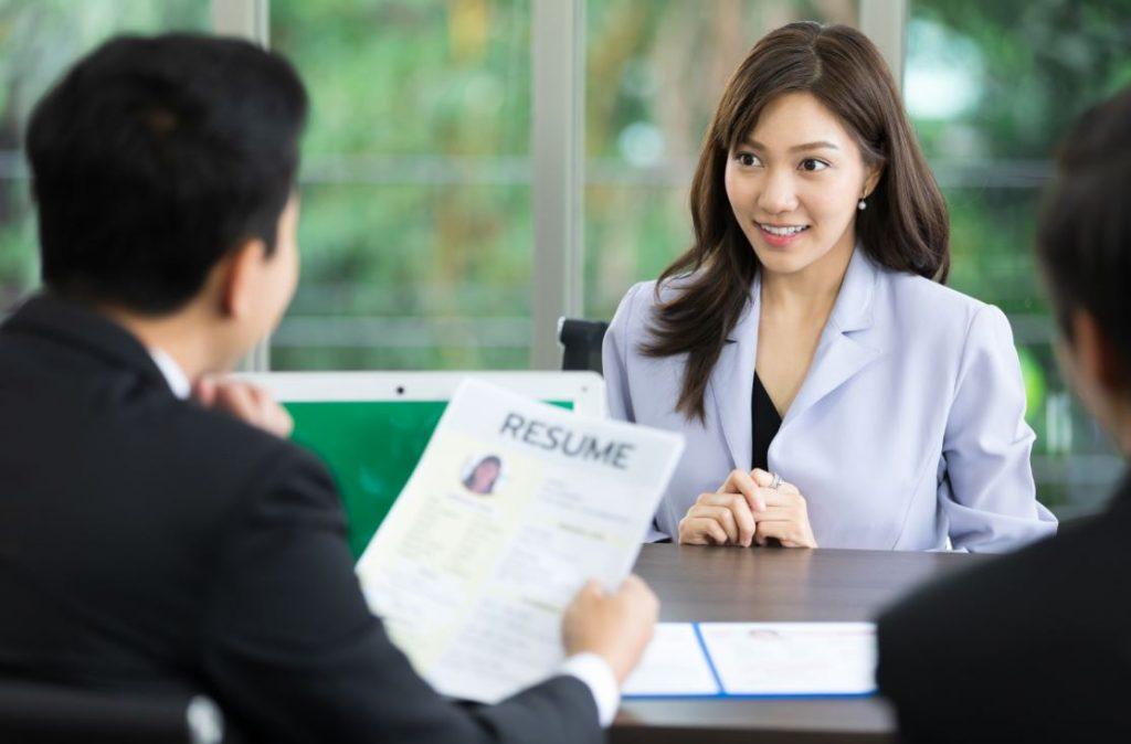 Candidate et recruteur lors d'un entretien d'embauche qui discutent du CV et de la lettre de motivation