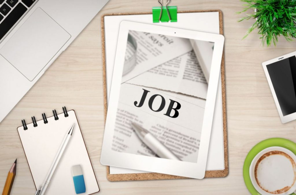 Eléments de travail disposés sur un bureau, avec un iPad pour la recherche d'emploi, idéal pour visualiser sa lettre de motivation !