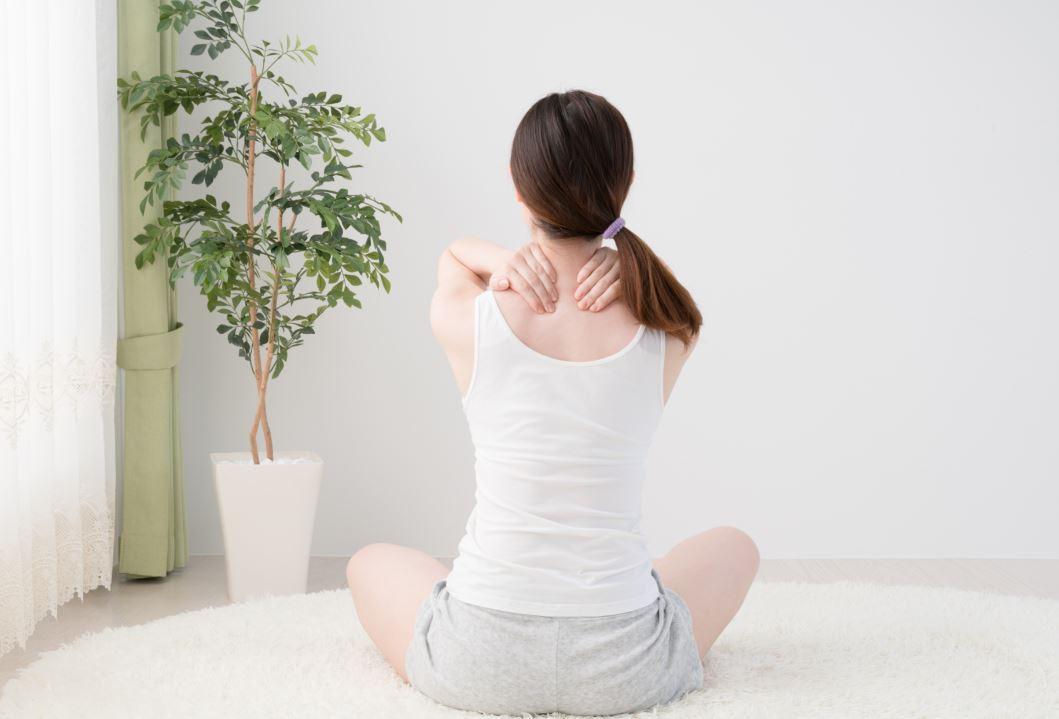 Femme de dos pratiquant un auto-massage pour réduire le stress